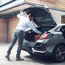 Muž otvára batožinový priestor v zadnej časti modelu Honda Civic 5D