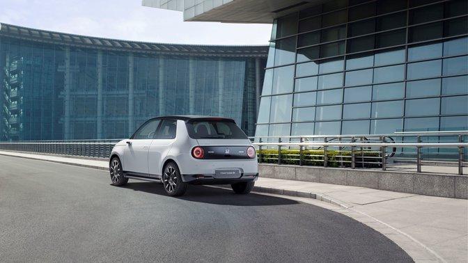 Trojštvrťový záber zozadu na model Honda e so sklenenými budovami v pozadí