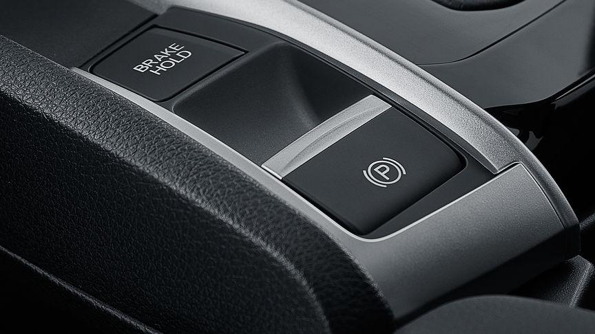 Detailný záber na tlačidlo podržania brzdy 4-dverovej Hondy Civic.