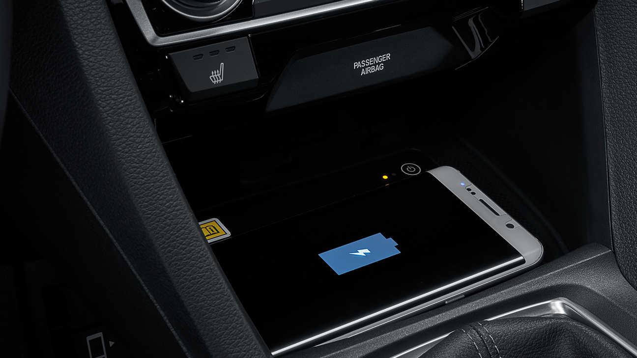 Detailný záber na bezdrôtovú nabíjačku telefónov modelu Honda Civic sedan.