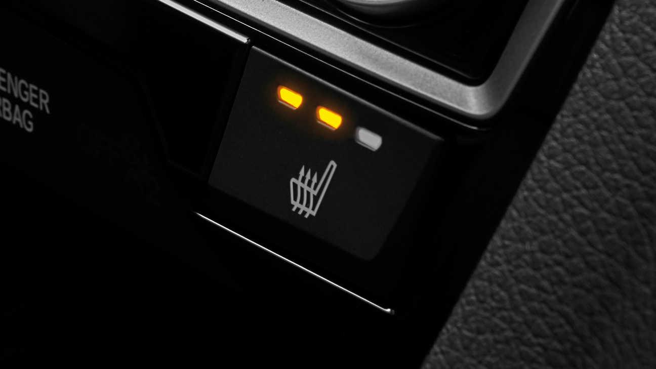 Priblížený pohľad na tlačidlo vyhrievaných zadných sedadiel modelu Honda Civic sedan.