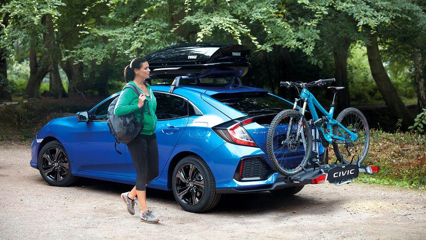 Trojštvrťový pohľad zozadu na 5-dverovú Hondu Civic s nosičom na bicykle.