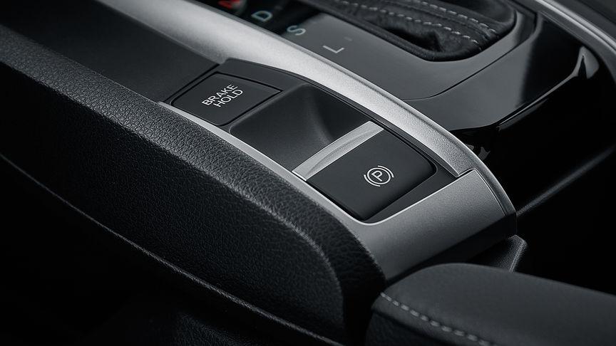 Detailný záber na tlačidlo podržania brzdy.