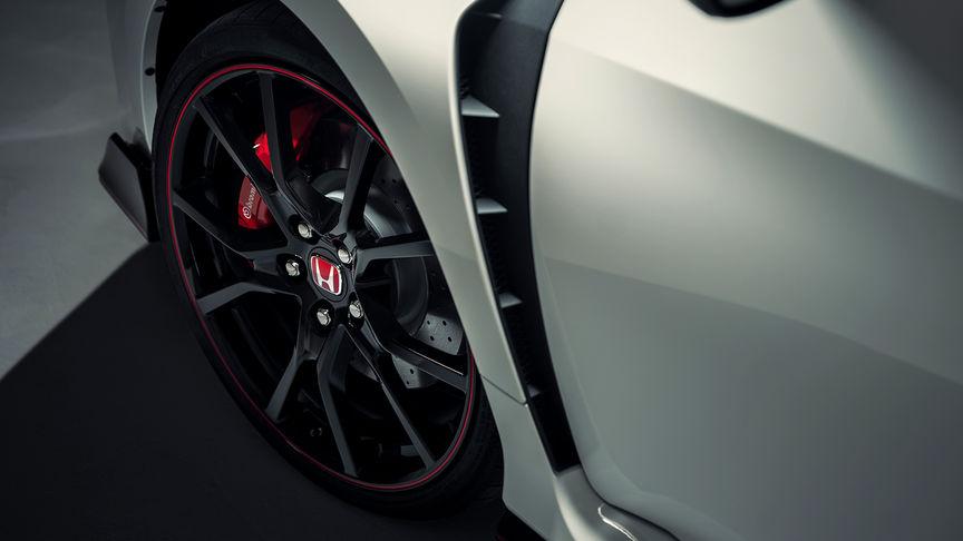 Predný trojštvrťový detailný pohľad na model Honda Civic Type R a zliatinové disky.