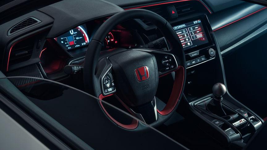Priblížený pohľad na kožený volant modelu Honda Civic Type R s červenou a titánovo-striebornou dekoráciou.