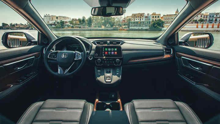 Pohľad na palubnú dosku v interiéri vozidla Honda CR-V Hybrid s širokým výhľadom na ulicu.