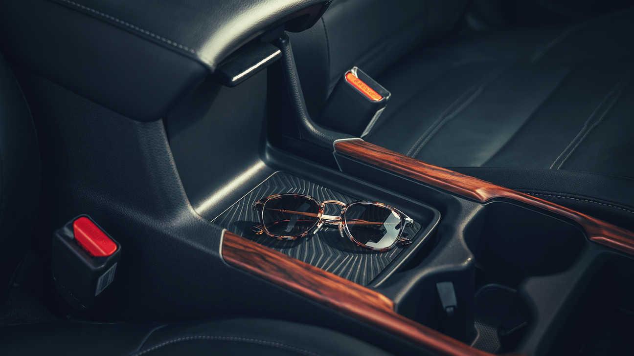 Detailný bočný záber na kryt s odkladacou plochou a úložným priestorom v konzole vozidla Honda CR-V Hybrid.