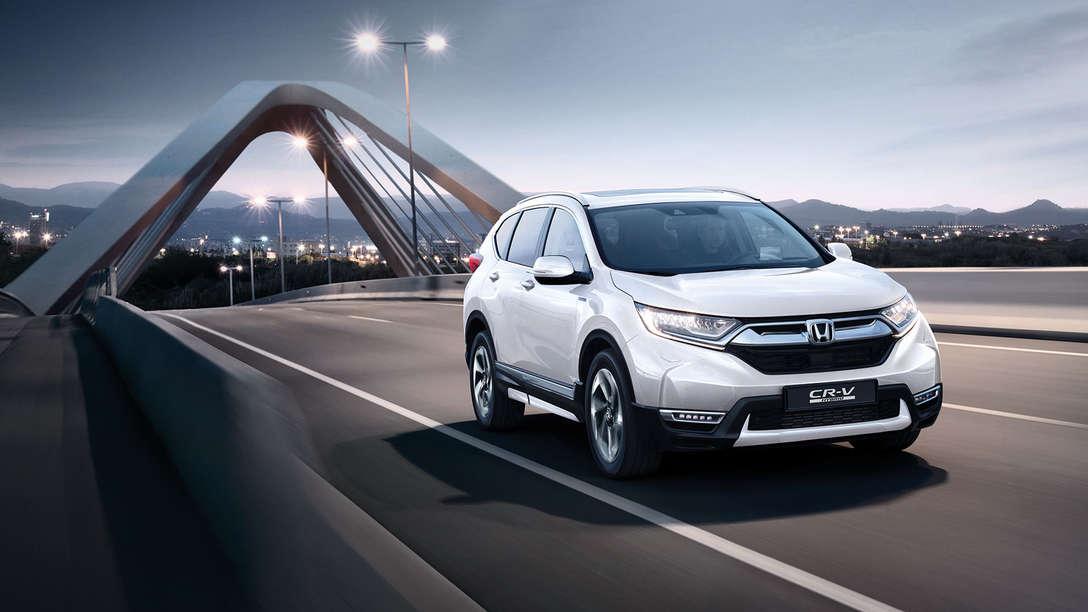 Trojštvrťový pohľad spredu na vozidlo Honda CR-V Hybrid idúce po ulici.