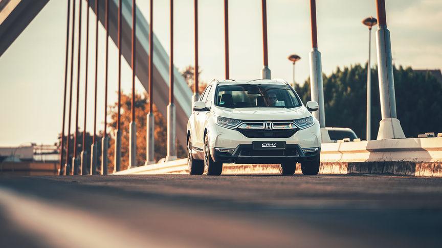 Trojštvrtinový pohľad spredu na vozidlo Honda CR-V Hybrid na ulici.