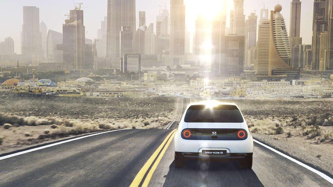 Rear facing Honda e driving into the city.
