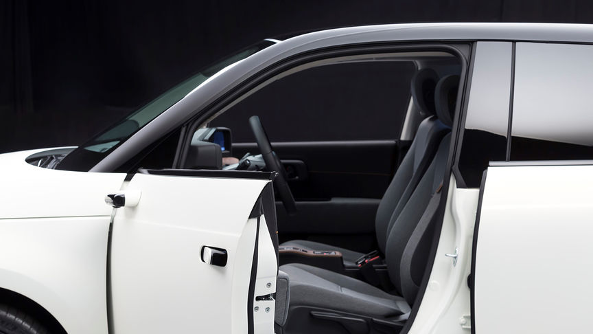 Side facing Honda e with open front door.
