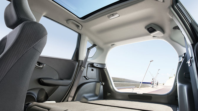 Predný trojštvrťový pohľad na model Honda Jazz na veternej ceste vhorách.
