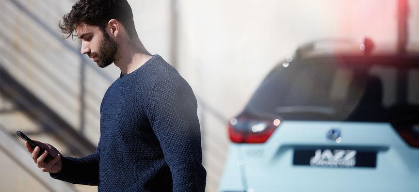 Muž prezerajúci si aplikáciu My Honda+ s modelom Honda Jazz Hybrid Crosstar v pozadí.