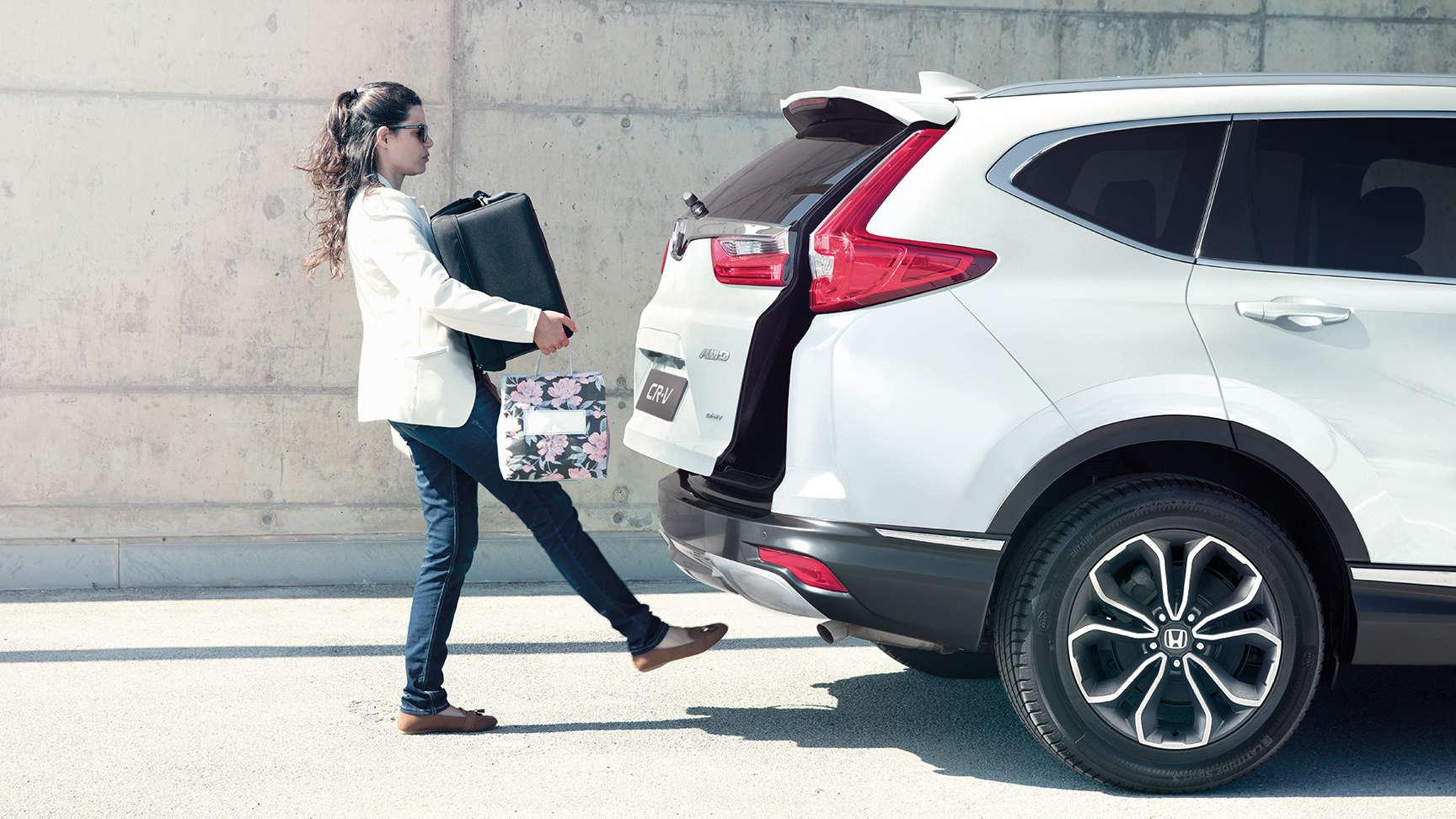Žena pri nakladaní batožiny do zadnej časti vozidla CR-V