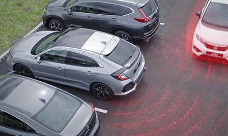 Vozidlo so systémom Honda Sensing na parkovisku s ilustráciou upozornenia na vozidlá blížiace sa z boku a systému pre elimináciu mŕtveho uhla.