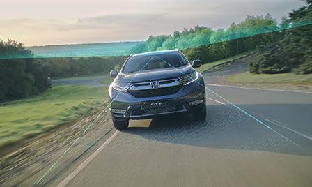 Vozidlo so systémom Honda Sensing na vidieku s ilustráciou systému pre zmiernenie rizika opustenia komunikácie a systému rozpoznávania dopravných značiek.