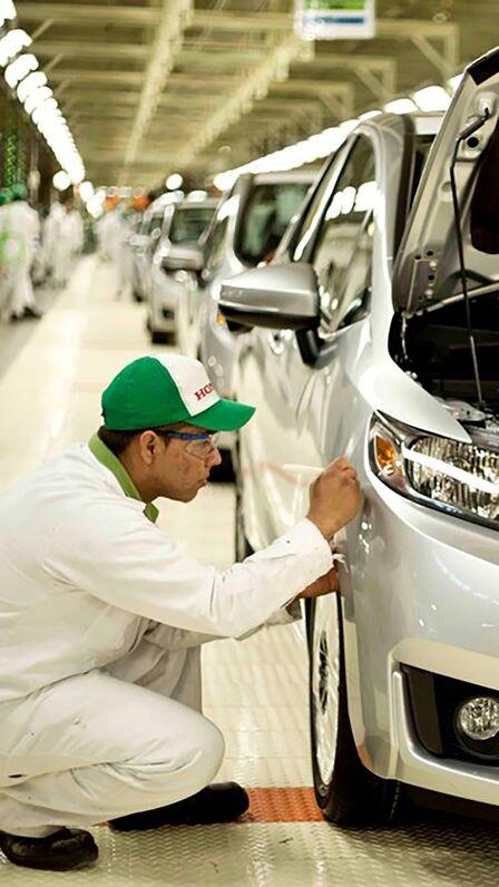 Technik spoločnosti Honda pracujúci na automobile vtovárni.