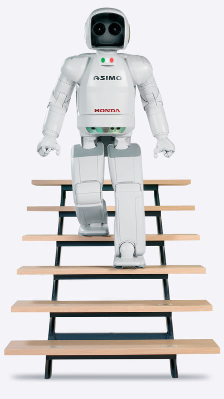 Záber spredu na robota ASIMO kráčajúceho dolu schodmi.