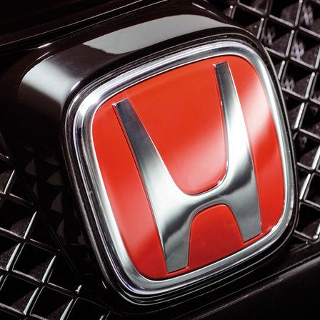 Detailný záber červeného loga H značky Honda.