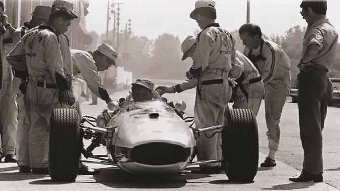 Automobil Honda Formula One zo šesťdesiatych rokov spilotom atechnikmi (záber spredu)
