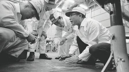 Soičiro Honda aniekoľko pracovníkov továrne vbielych kombinézach.