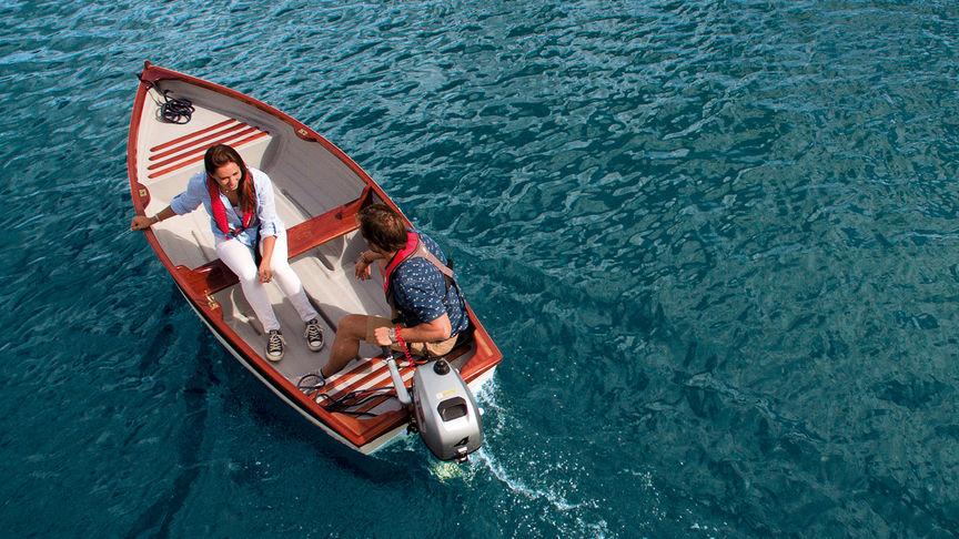 Muž a žena v člne používajúci motor BF2.3 na pohon člnu vpred