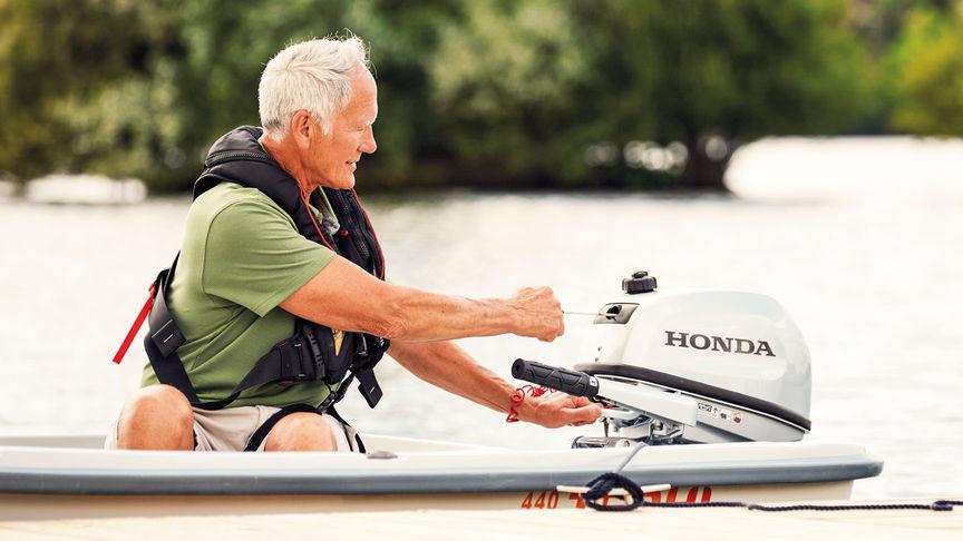 Používateľ na člne pri štartovaní motora.