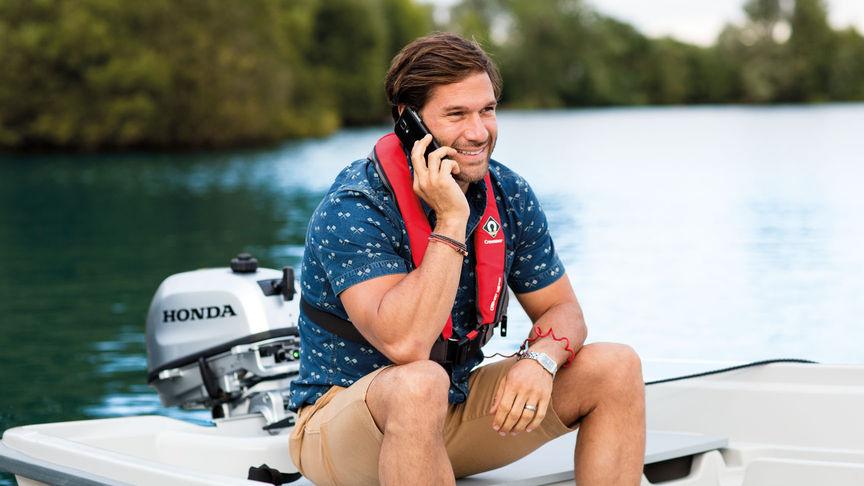 Používateľ s mobilným telefónom na člne.