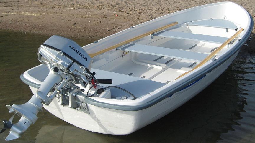 Čln na piesku s upevneným motorom Honda.