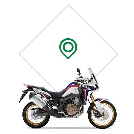Logo Honda s krídlom na červenej nádrži motocykla.