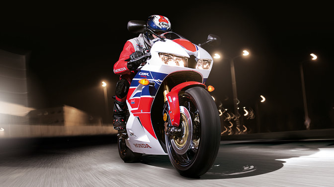 Front three quarter view of Honda CBR600RR and rider in dark location.